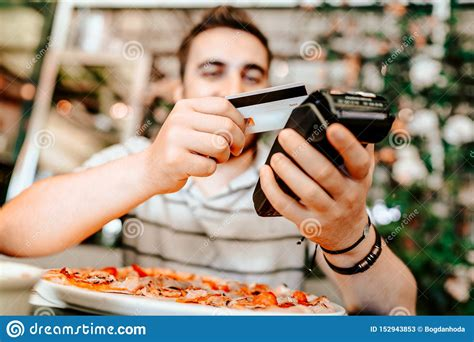 Using a credit card for bills can be helpful if you need to pay your rent or heating bill, but payday isn't until next week. Smiling Man Paying At Restaurant Using Smartphone. Mobile Paying Technology With Contactless ...