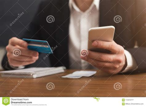 Both companies sell devices and services that allow individuals to take credit card payments from others through a smartphone. Man`s Hands Holding A Credit Card And Using Smartphone Stock Image - Image of credit, retail ...
